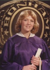 Judith's daughter, Jennifer, wearing a  graduation gown holding her diploma.