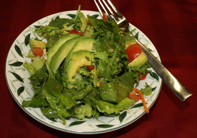 A green salad with avocados and tomatoes added with a shiny coating of ginger dressing to help lower cholesterol