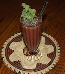 smoothie with a generous topping of chia seeds, garnished with leaf of kale
