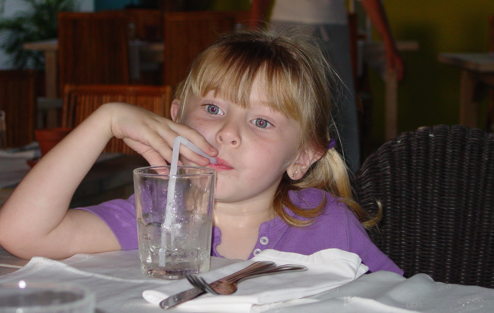a cute little girl at the dinner table drinking a cool glass of water.
