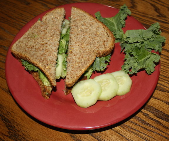 A tasty avocado cucumber sandwich with kale on sprouted grain bread