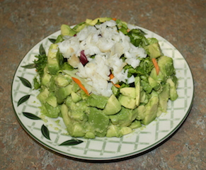 this is the finished avocado salad topped with flaky white fish, before dressing or sauce is added
