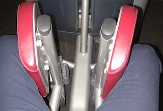 somebody sitting on exercise equipment chair pushing weights in with knees