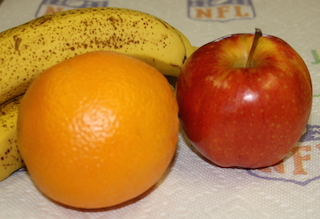 speckled banana, an orange and an apple - a healthy treat to start the day