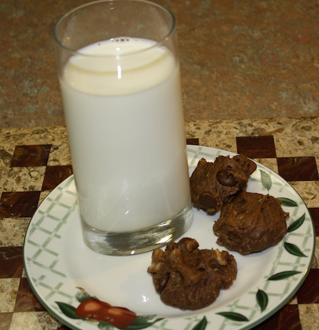 chocolate chip avocado cookies on a plate with a tall cool glass of milk.