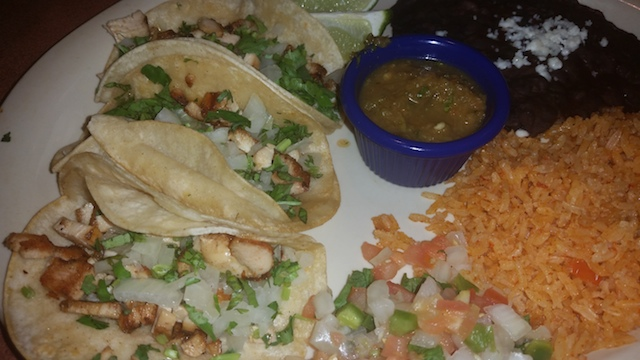 Chicken tacos with cheese vegetables and salsa served with rice and beans
