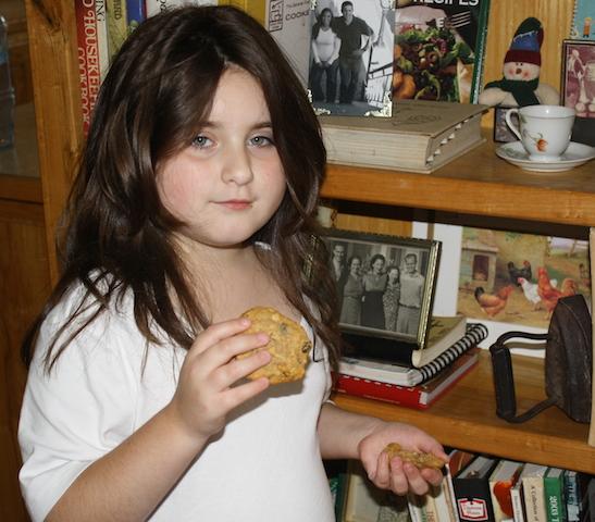 Ella eating a freshly baked oatmeal cookie.