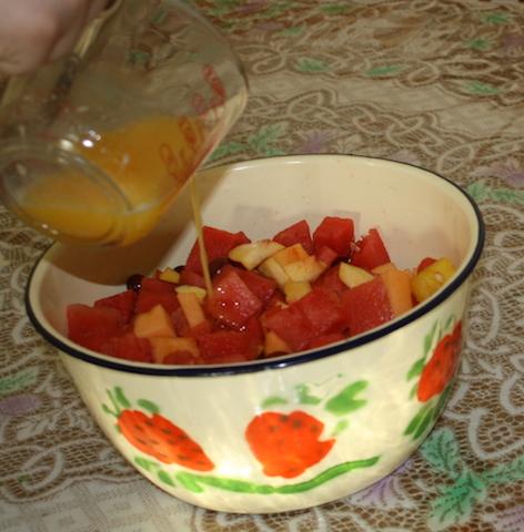 Pouring orange juice over salad