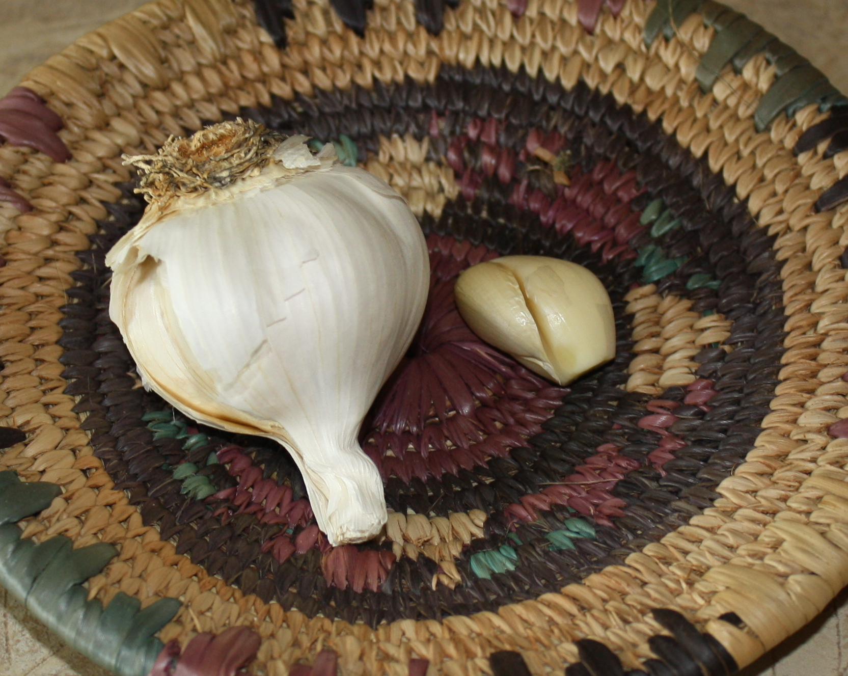 A basket containing a pod and clove of garlic. 4 cloves a day helps normalize cholesterol