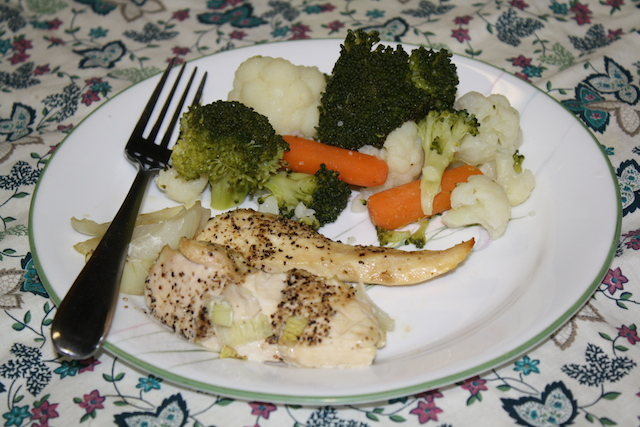 baked chicken and steamed onions, cauliflower, broccoli and carrots on a dinner plate