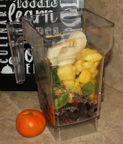 the blender container full of fresh fruits and spinach and almonds