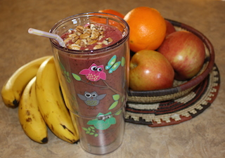 A bright rose colored smoothie topped with nuts sitting on the counter by some fruit makes you hungry