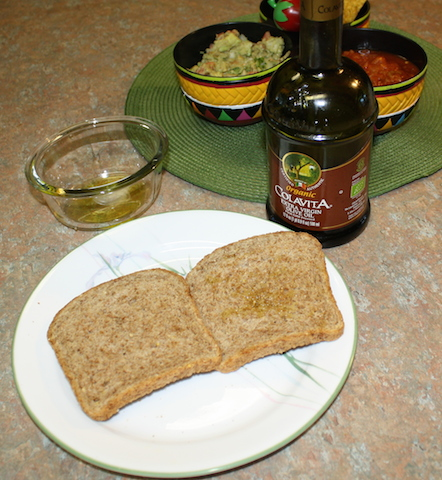two pieces of sprouted grain bread spread with olive oil.