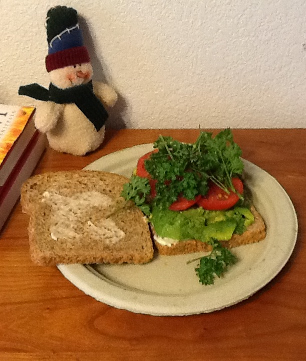 A yummy avocado sandwich with parsley and sliced tomatoes on a paper plate. A quick lunch when you are busy.