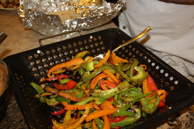 Red, yellow, green and orange peppers cooked in a basked on the barbecue