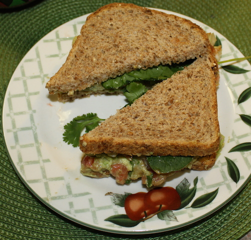 A lovely sandwich made on sprouted grain bread filled with colorful homemade guacamole