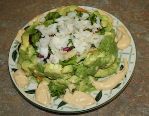 avocado salad with a ring of avocados surrounding a crispy filling of field greens topped with flaky cod with a little sauce on  the plate to use as you desire