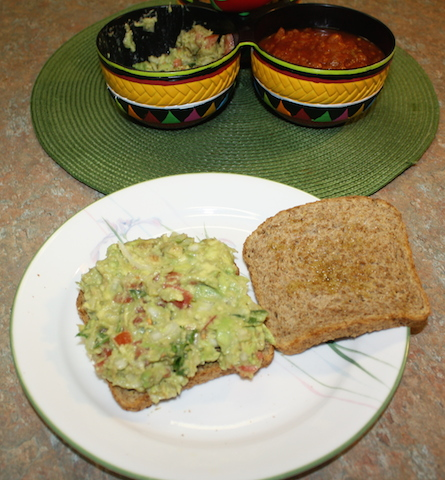 Two pieces of sprouted grain bread spread with colorful delicious guacamole