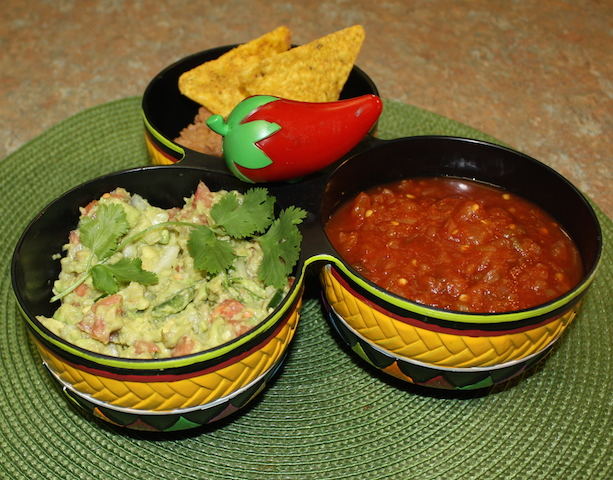 three bowls with a decorative red pepper connecting them.  One bowl contains homemade salsa, one contains my favorite yummy guacamole recipe and the other contains bean dip. happy dipping