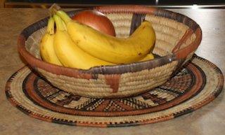 a decorative handmade African basket containing a bunch of bananas and another fruit