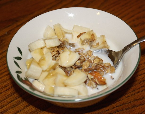 a small bowl of homemade granola topped with bananas and nuts with almond milk