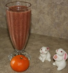 two cute bunny salt shakers by a mandarin orange smoothie and a ripe mandarin orange