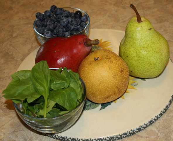 Three varieties of pears with some blueberries in a small bowl and some spinach