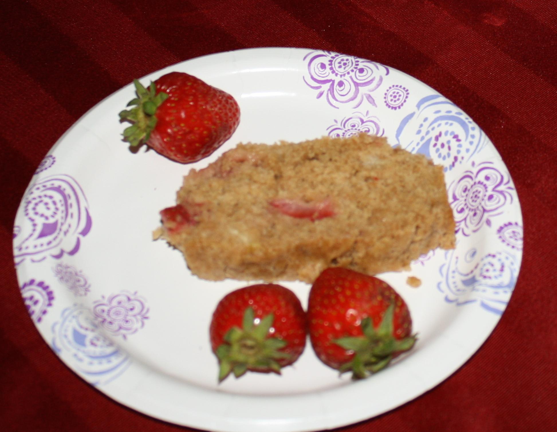 a slice of strawberry banana bread garnished with three fresh strawberries