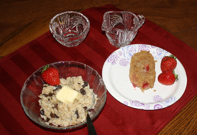 A creamy bowl of oatmeal with raisins and almonds and chia seeds served with strawberry bread for healthy cholesterol